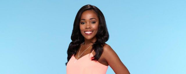 Jasmine Goode smiles in a pink shirt behind a blue background.