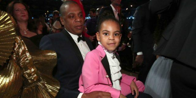 Blue Ivy is sitting on Jay-Z's lap in a pink suit.