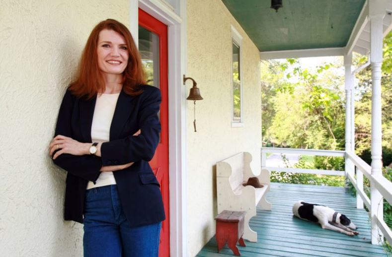 Jeannette Walls leaning up against a house standing on a porch with a dog in the background