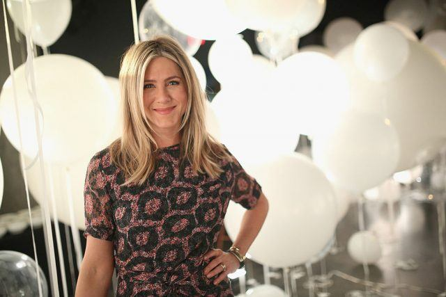 Jennifer Aniston stands in front of white balloons at a charity event.