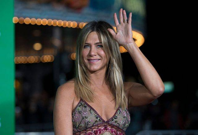 Jennifer Aniston waves at the paparazzi at a movie premiere.