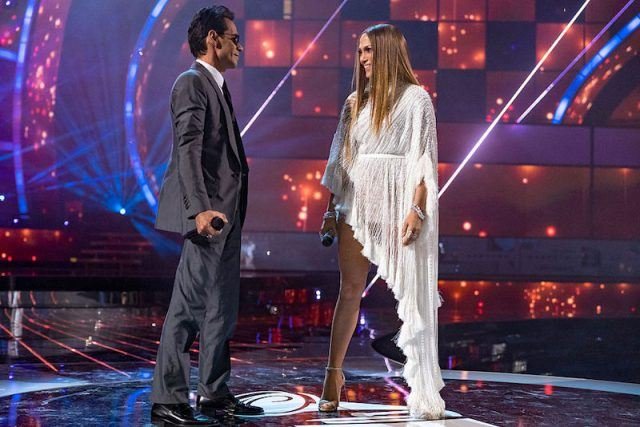 Marc Anthony and Jennifer Aniston performing a song onstage.