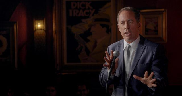 Jerry Seinfeld holds a microphone during a stand up routine.