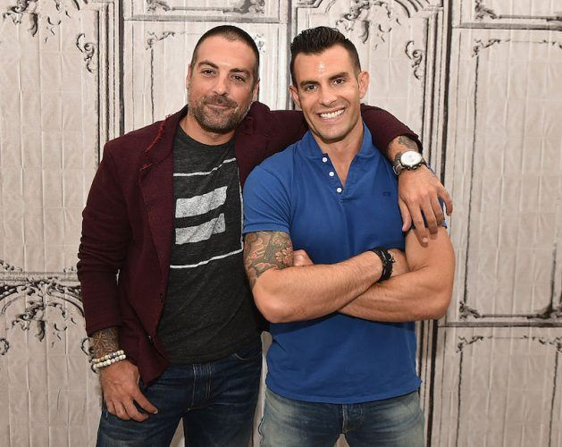 Anthony Carrino and John Colaneri posing in front of a decorative wall.