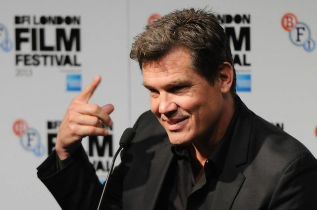 Josh Brolin speaks into a microphone and points upwards at the press conference for 'Labor Day' during the 57th BFI London Film Festival.