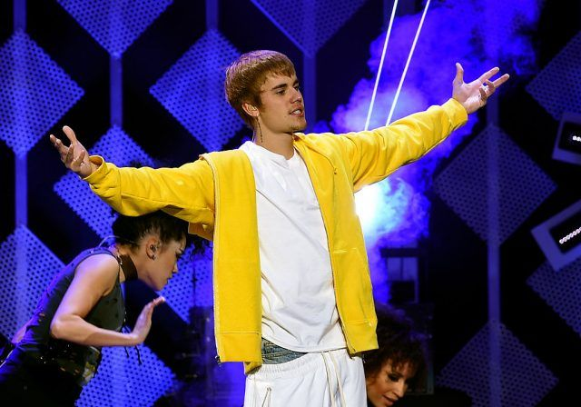 Justin Bieber performing on stage in a yellow hoodie.