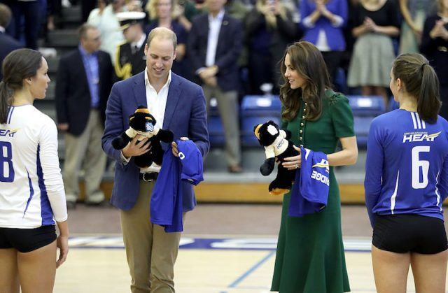 Prince William and Kate Middleton accept gifts at a basketball game.