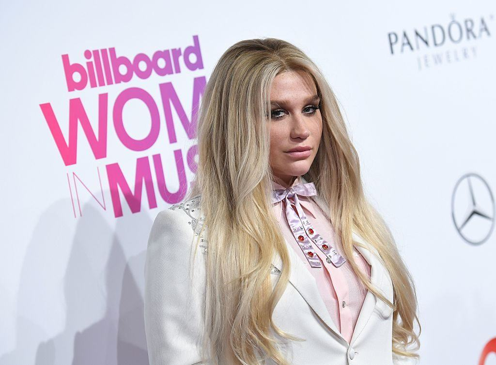 Kesha poses on the red carpet in a white jacket.