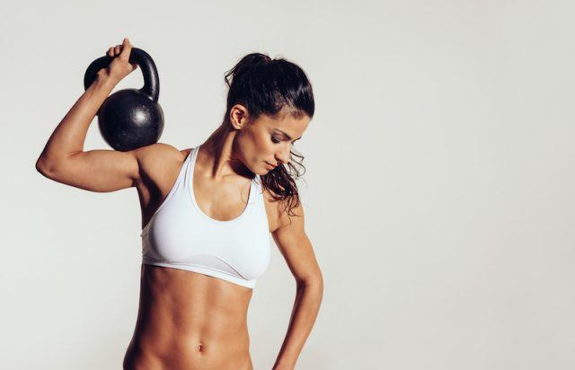 A woman does a workout using a kettlebell in front of a white background.