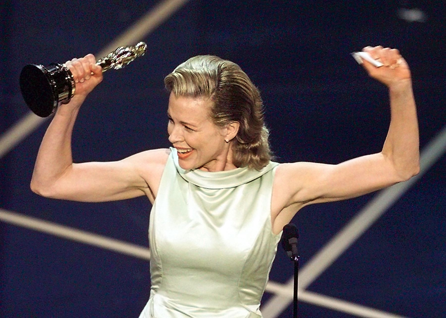"""Actress Kim Basinger holds up her Oscar after winning the Best Supporting Actress Oscar for her role in """"L.A. Confidential"""" during the 70th Academy Awards at the Shrine Auditorium 23 March."""