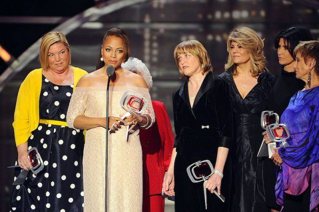 Kim Fields holds an award on stage with the cast members of 'The Facts of Life'.