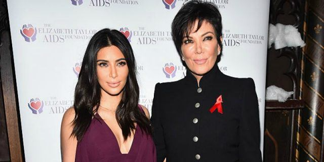 Kim Kardashian and Kris Jenner pose together on the red carpet.