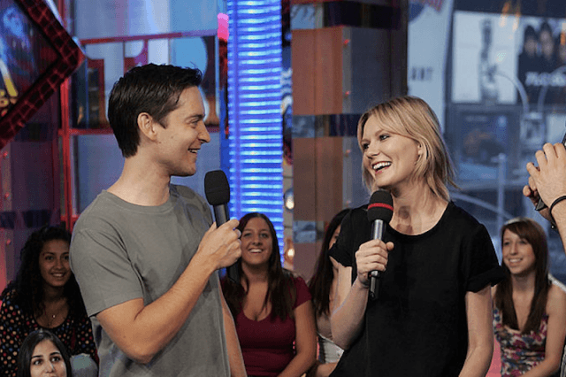 Toby Maguire and Kirsten Dunst hold up microphones while being interviewed on camera.