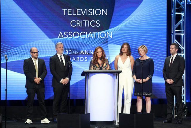 Leah Remini stands onstage at the Television Critics Association with her show's producers and cast members.
