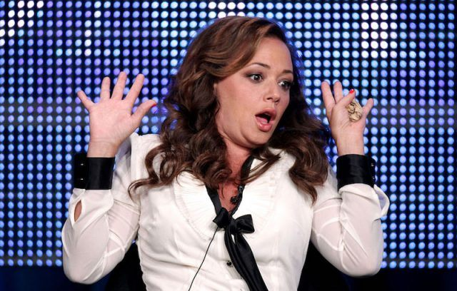 Leah Remini sits onstage during the Summer TCA Tour in a white and black shirt.