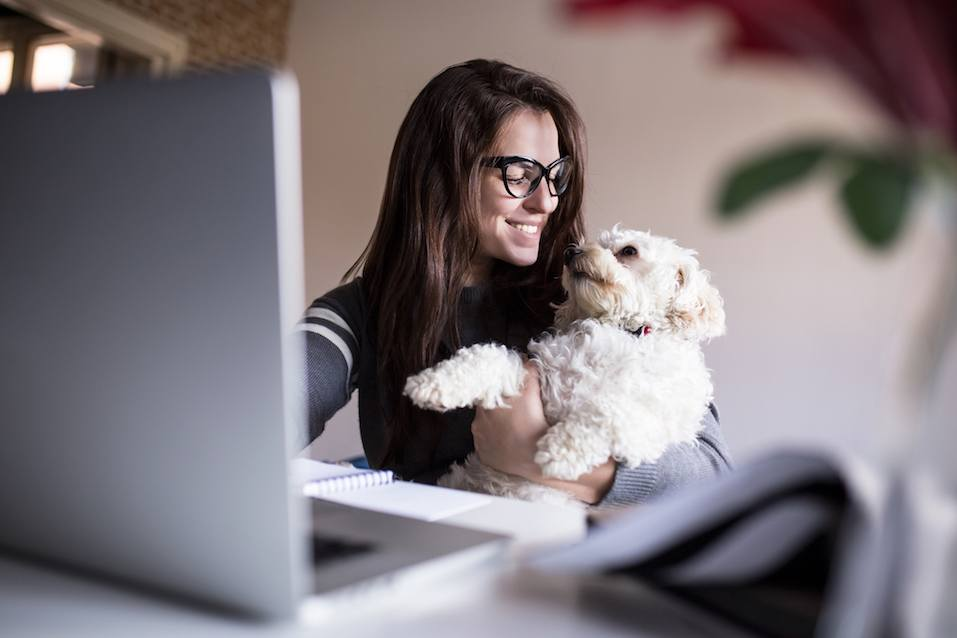 Woman and her dog at her home office hugging