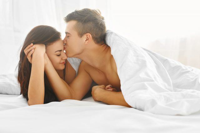 A couple in bed, a man kisses his partner's forehead.
