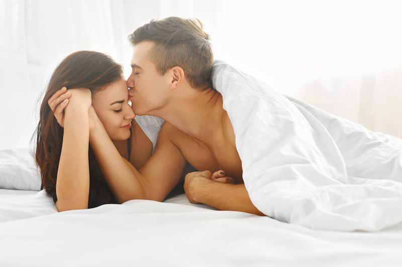 couple kissing each other under the bed covers