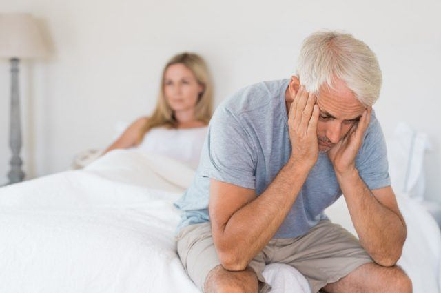 Man sits down at the edge of his bed while his partner lies down.