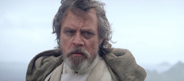 Luke Skywalker standing in a gray jacket on a cliff.