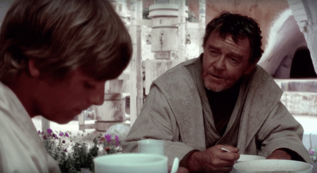 Owen speaks to a young Luke while sitting at a table in A New Hope