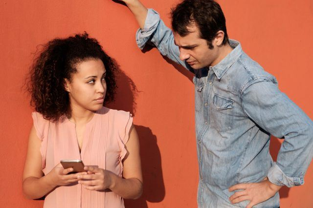 A woman looks over at a man who is peeking at her phone.