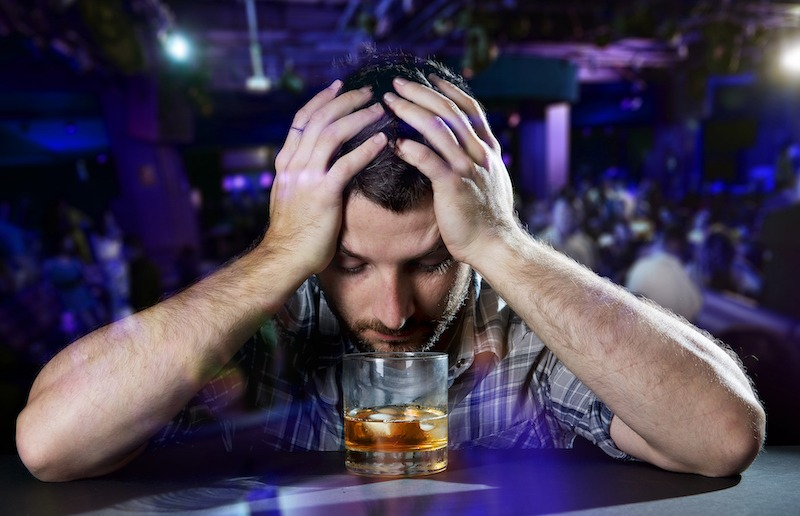 a man staring into a glass of brown alcohol