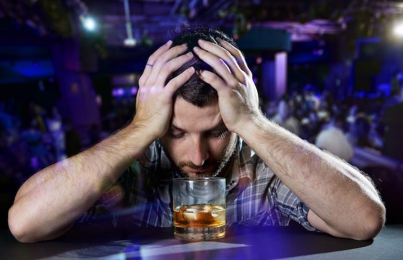 man at a bar looking sad