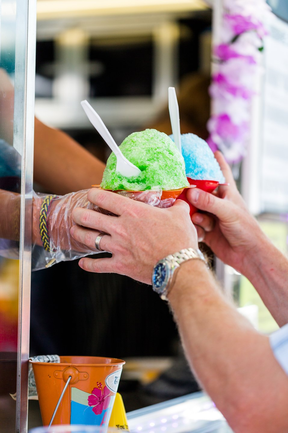 Man getting two snow cones from vendor