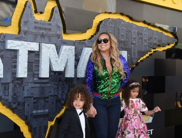 Mariah Carey holds the hands of her two children while attending a movie premiere