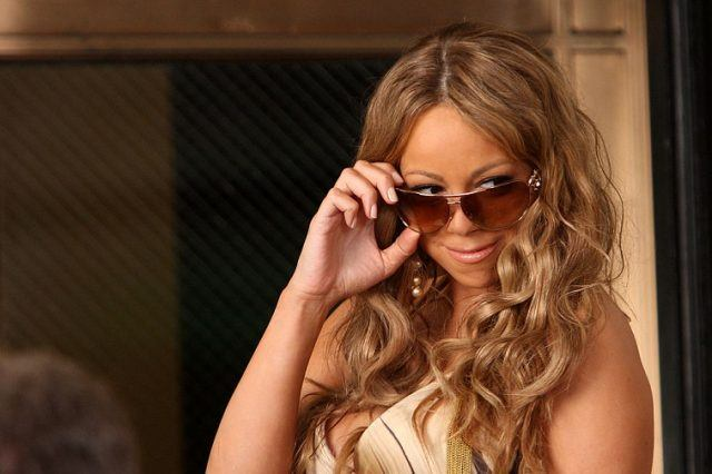 Mariah Carey pulls her sunglasses down while filming a music video