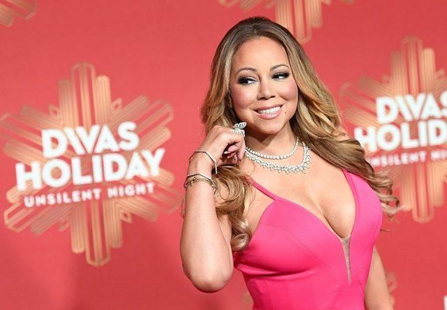 Mariah Carey poses on the red carpet before holiday show