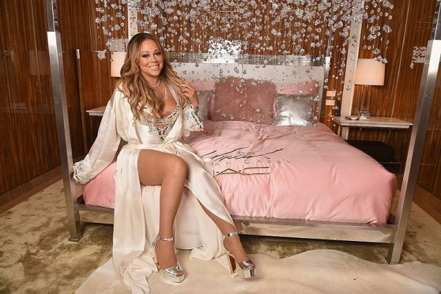 Mariah Carey posing on bed in a robe for makeup launch