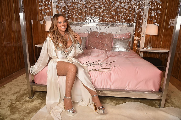 Mariah Carey posing on bed for makeup launch