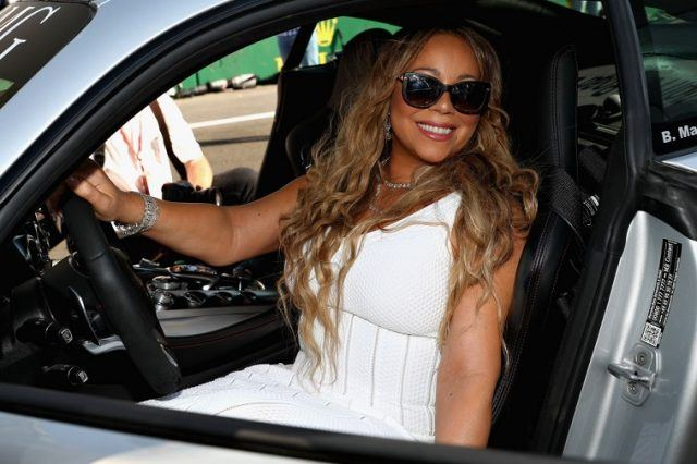 Mariah Carey smiling for photos while in a car behind the steering wheel in Baku, Azerbaijan