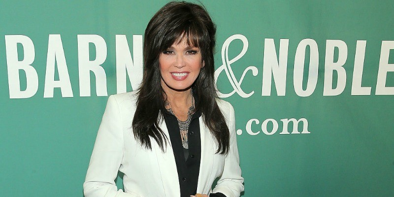 Marie Osmond poses in a white jacket on the red carpet.