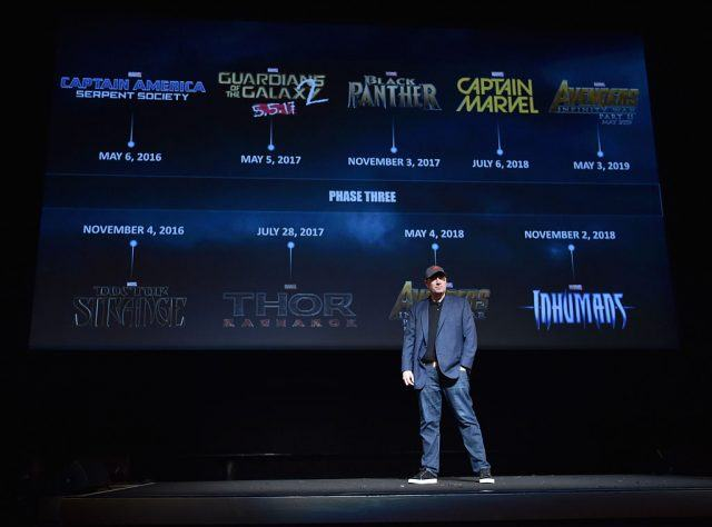 Kevin Feige stands on stage in front of a screen displaying the lineup of Marvel's new releases.