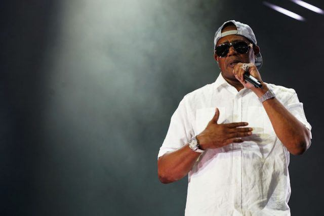 Master P holds a microphone while performing on stage.