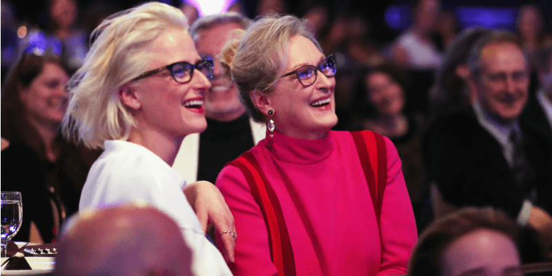 Meryl Streep and Mamie Gummer sit next to each other smiling and wearing the same kind of glasses.