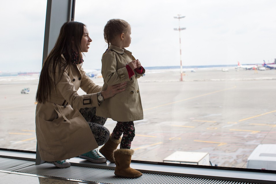 Mother and little daughter looking out the window at airport