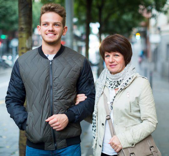 A mother and adult son walk together outside.