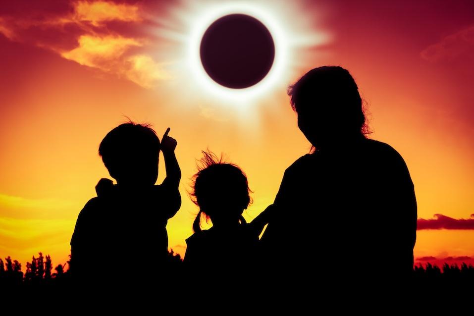 Boy point to solar eclipse on gold sky background