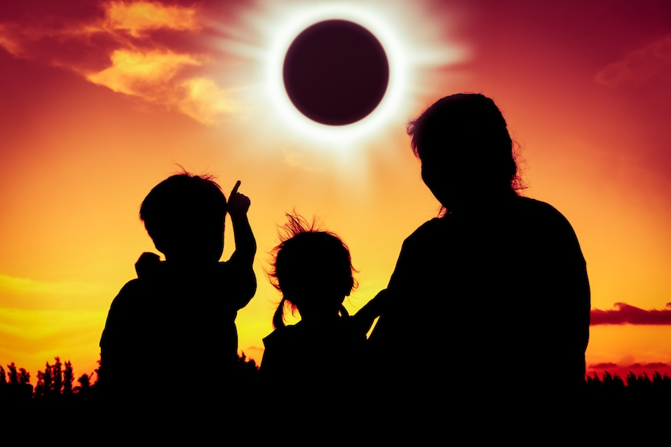 Boy point to solar eclipse on gold sky background