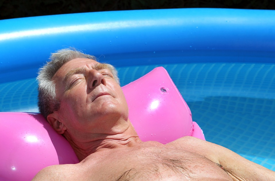 Older man sunbathing on lilo