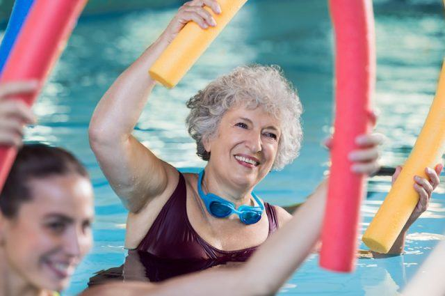 A woman does water aerobics in a pool.