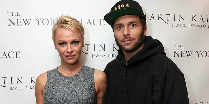 Pamela Anderson poses in a grey dress with Rick Salomon on the red carpet.