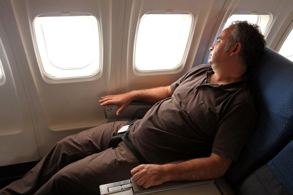Passenger looking through window in airplane