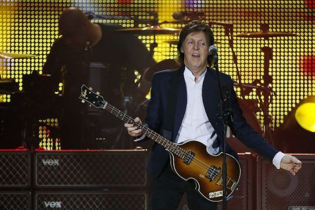 Paul McCartney playing his guitar and singing at a concert in France in 2015.