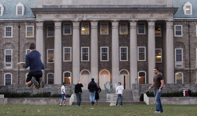 Penn State students play frisbee in front of Old Main
