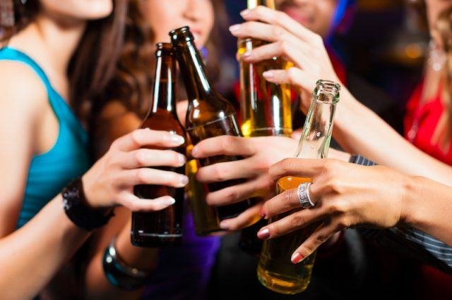 A group of people drink beers at a club.
